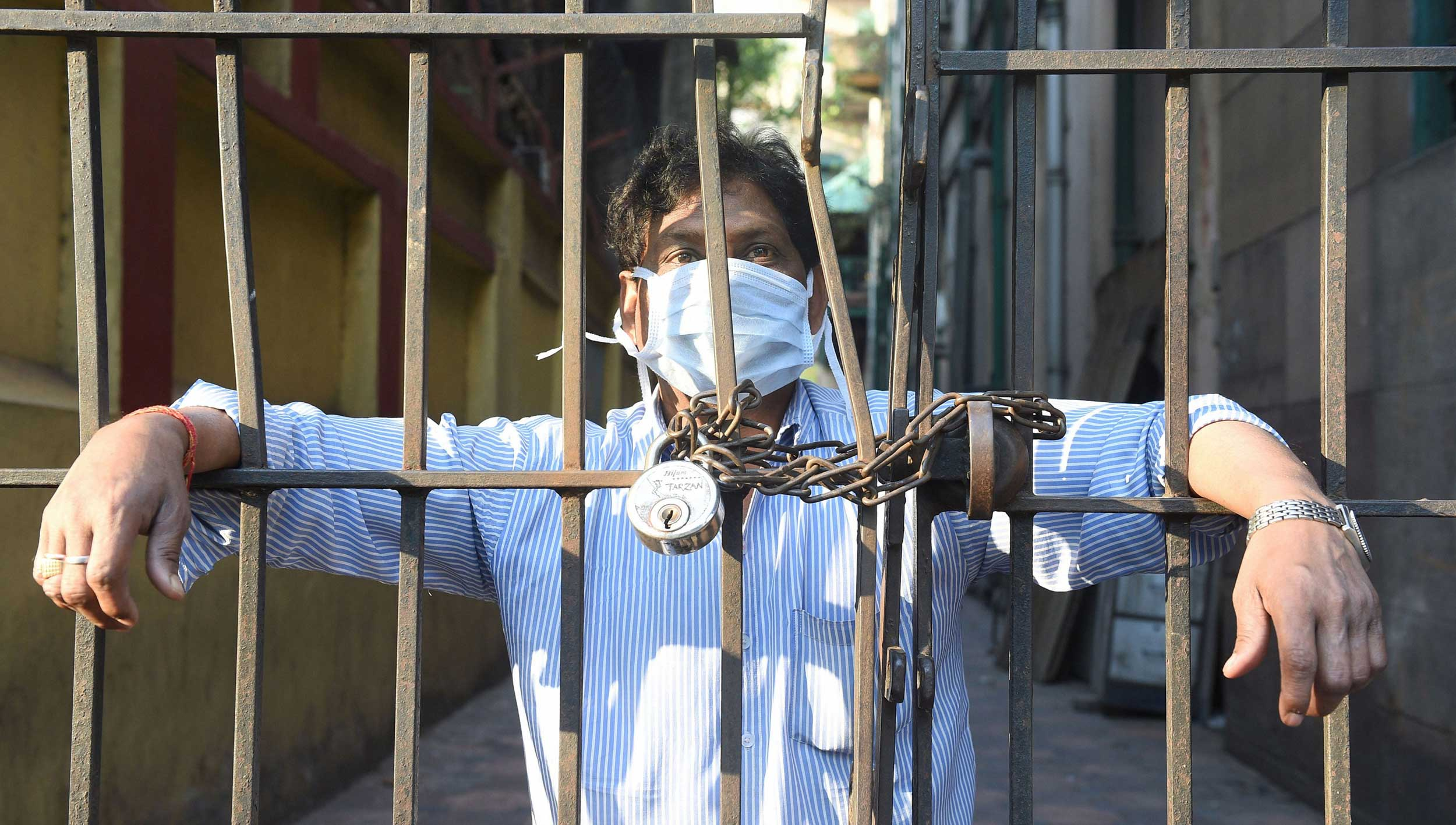 A man, wearing a mask, looks from a closed gate during the Covid-19 lockdown in Calcutta