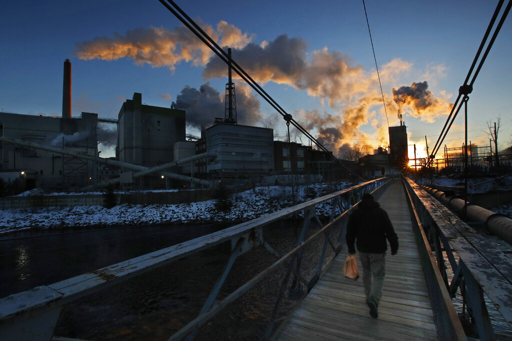 A worker crosses a pedestrian bridge on his way to work a shift at the ND Paper mill, on Thursday