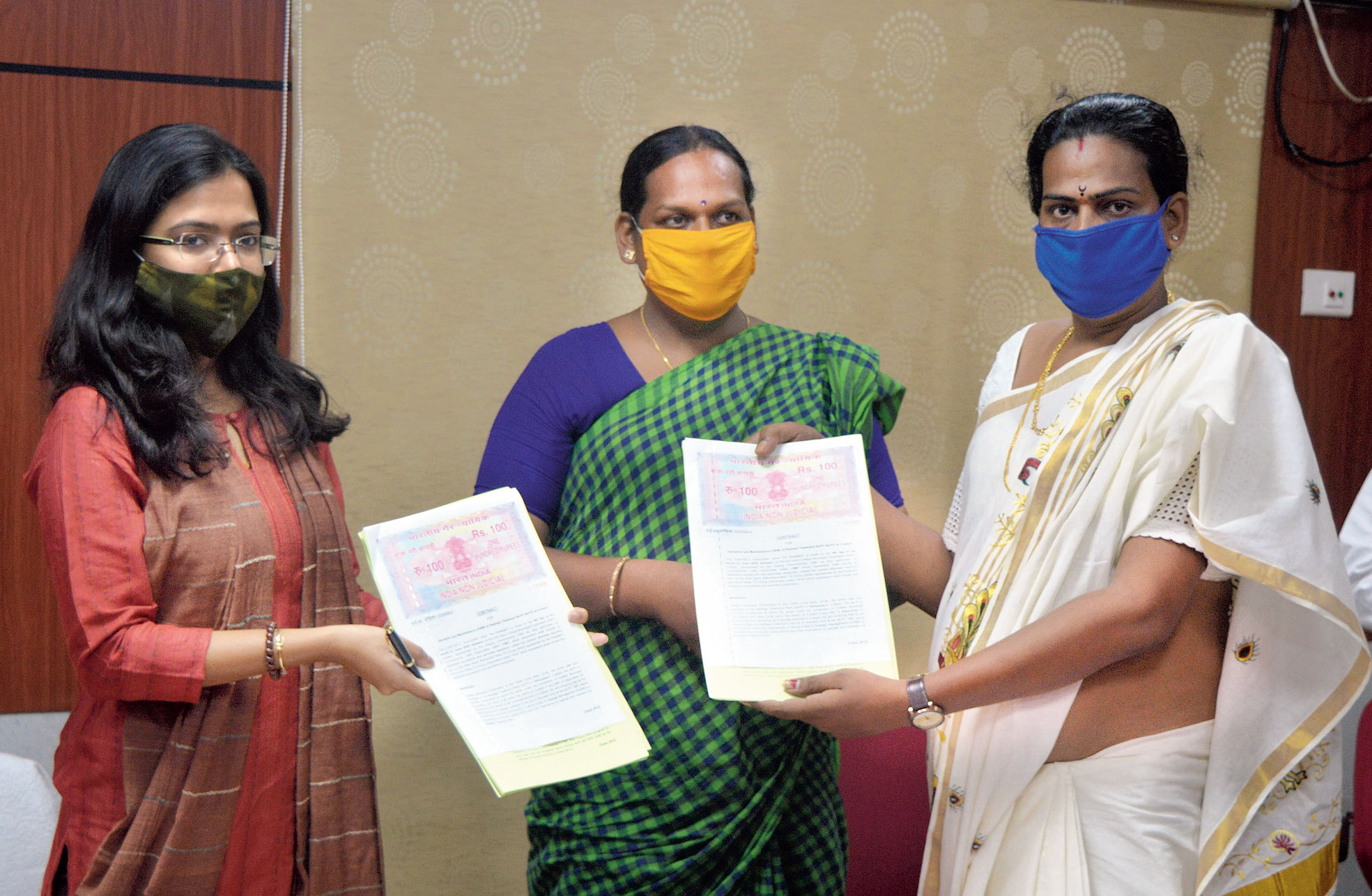 Transgender SHG members sign a contract with Cuttack Municipal Corporation commissioner Ananya Das  (left)