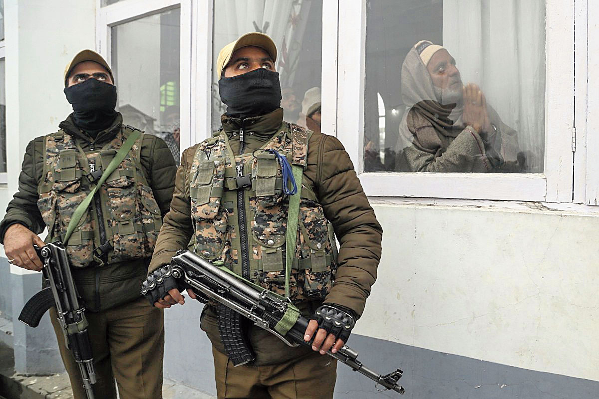 Security forces stand guard as Kashmiri Muslims pray in Srinagar on November  10, 2019.