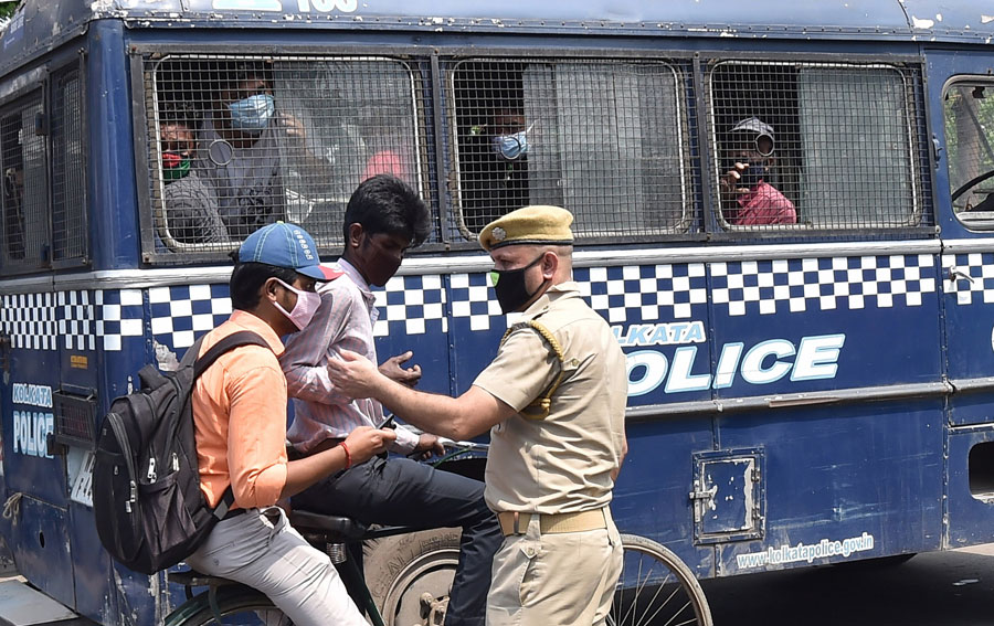 Police stop commuters for inquiry, as offenders who flouted the lockdown sit inside a prison van, during the nationwide lockout in wake of the coronavirus pandemic, in Calcutta on Friday,