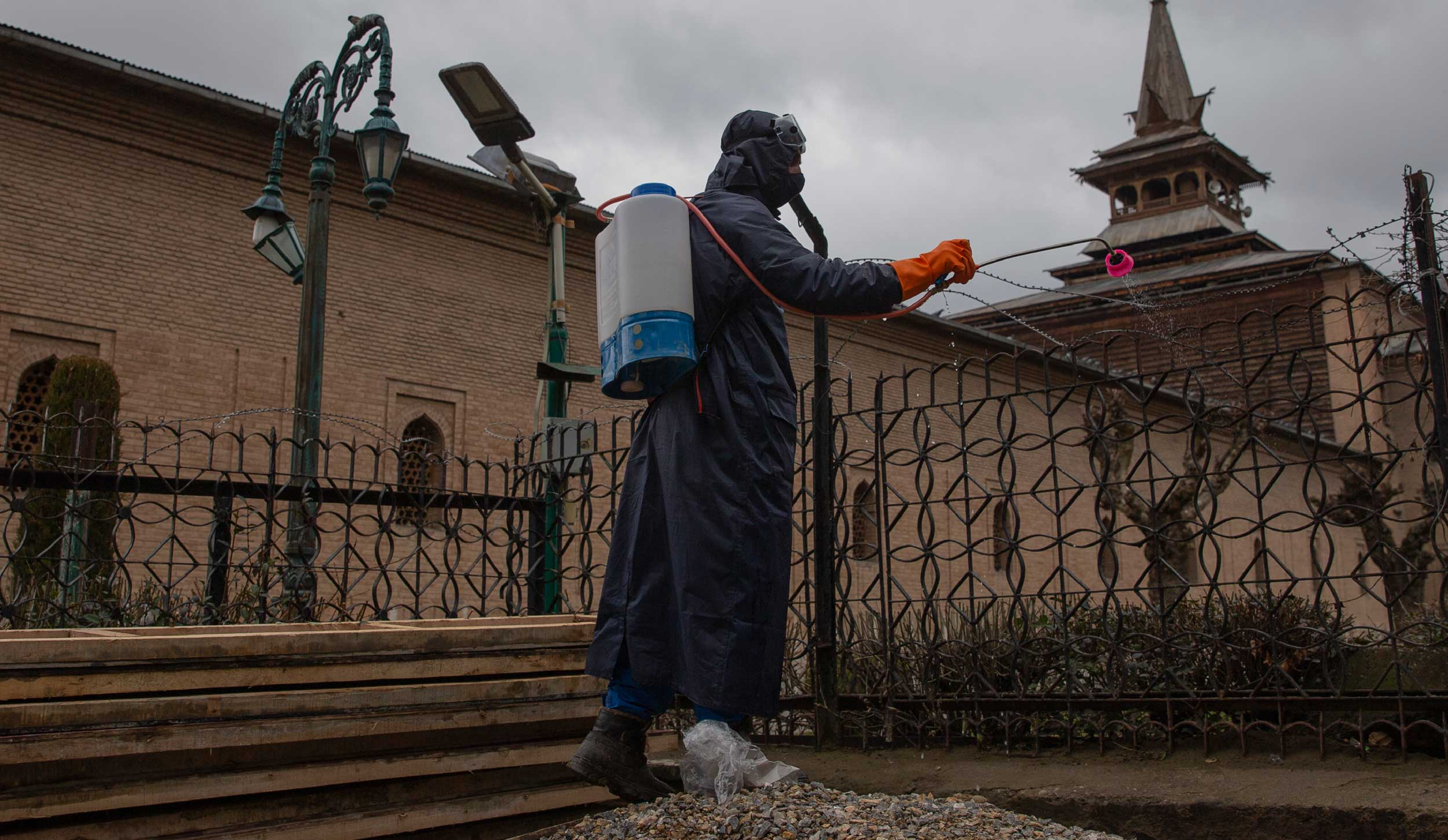A Srinagar Municipal Corporation staff sprays disinfectant outside Jamia Masjid in Srinagar on Friday.