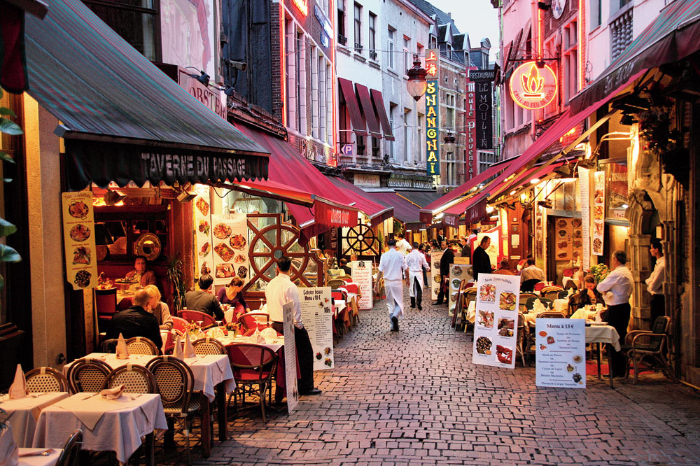 On both sides of Rue des Bouchers are tables for dining
