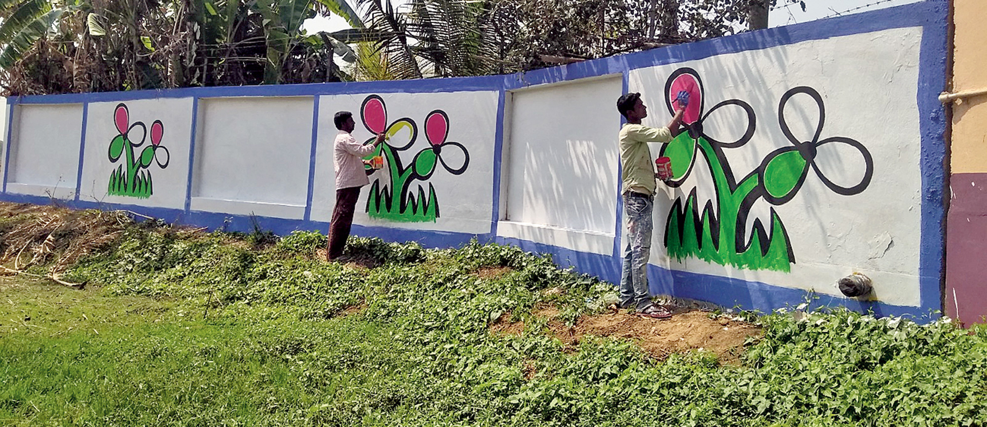 Trinamul workers paint the party's symbol on a wall in Birbhum's Parui.