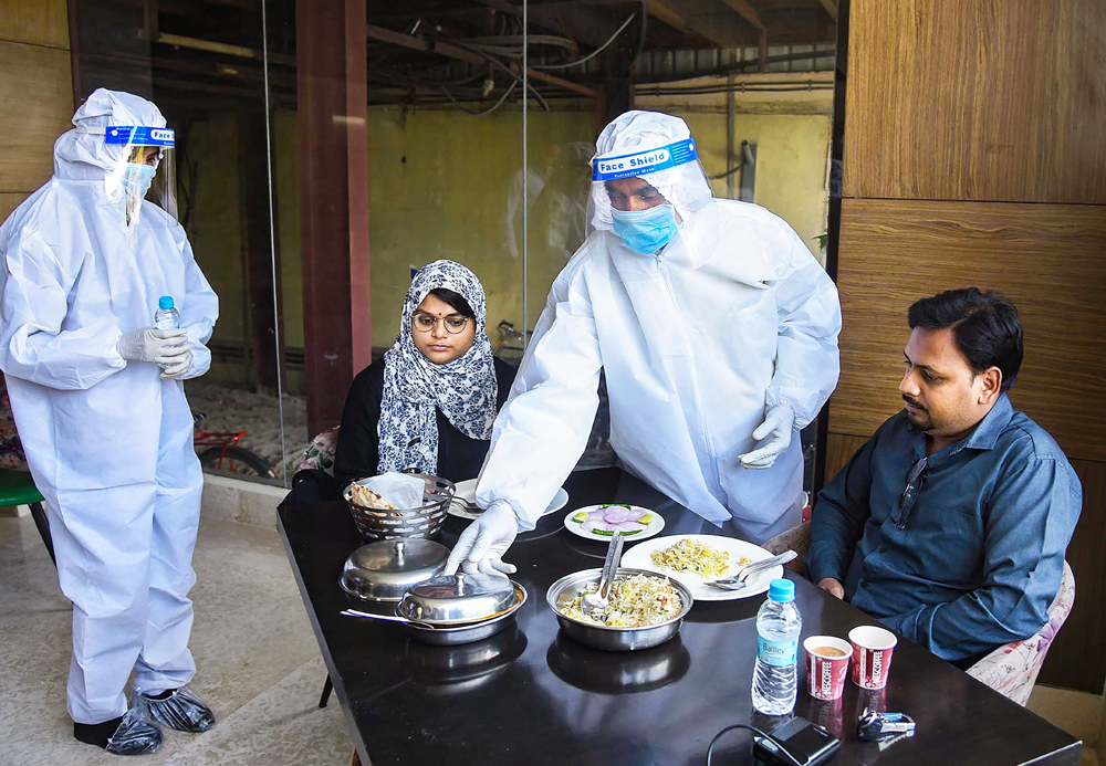 Waiters wearing PPE kits serve food to customers at a restaurant after the authorities permitted opening of eateries, during the ongoing Covid-19, lockdown, in Patna, Monday, June 8, 2020.