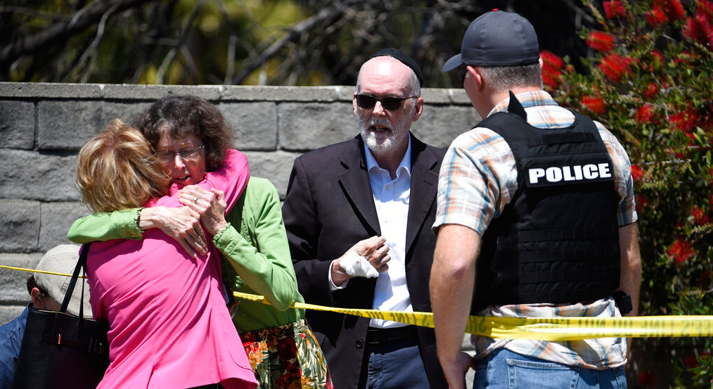 Two people hug as another talks to a San Diego County Sheriff's deputy outside of the Chabad of Poway synagogue, Saturday, April 27, 2019, in Poway, California.