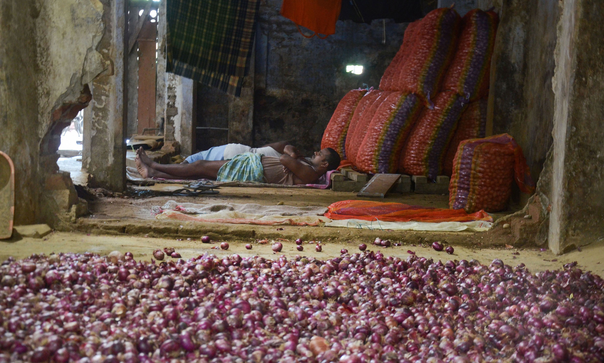 A labourer rests beside onion sacks at a market in Dibrugarh on September 28, 2019.