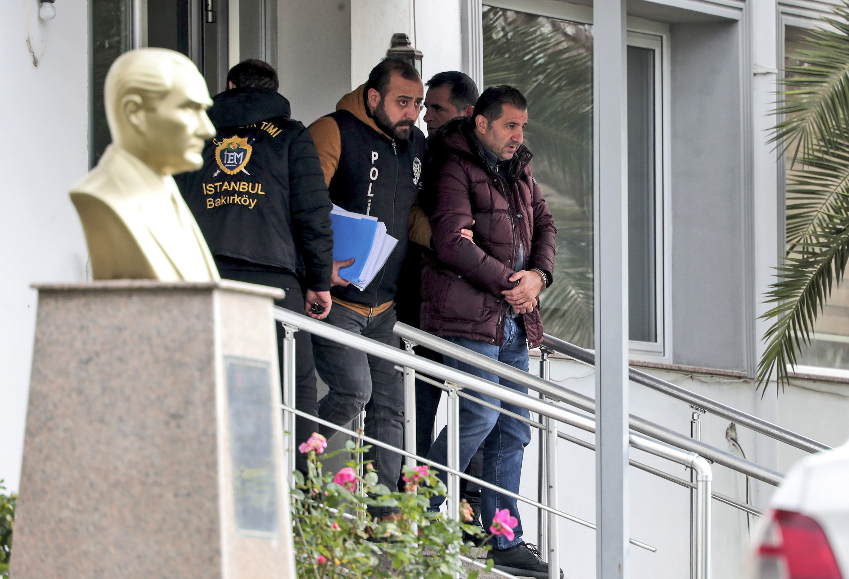 Turkish police officers escort suspects, accused of involvement of Nissan's former CEO Carlos Ghosn passage through Istanbul, after he fled Japan, in Istanbul, Friday, January 3, 2020