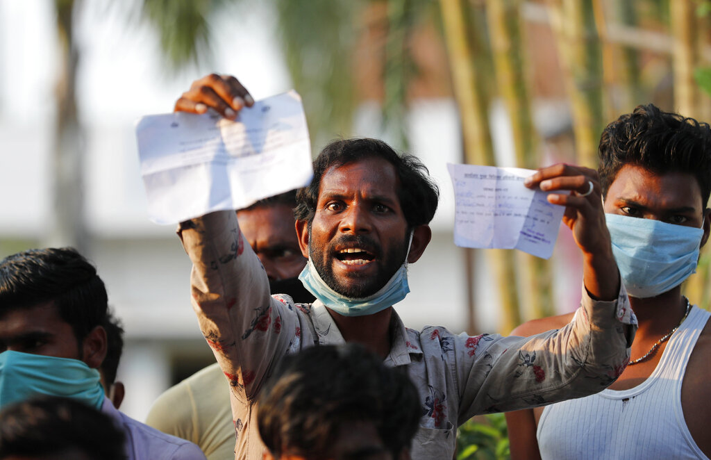 A laborer displays his identification as he protests against poor treatment at the quarantine center he has been kept in, along with others who arrived from outside the state, in Prayagraj, Wednesday, April 29, 2020.