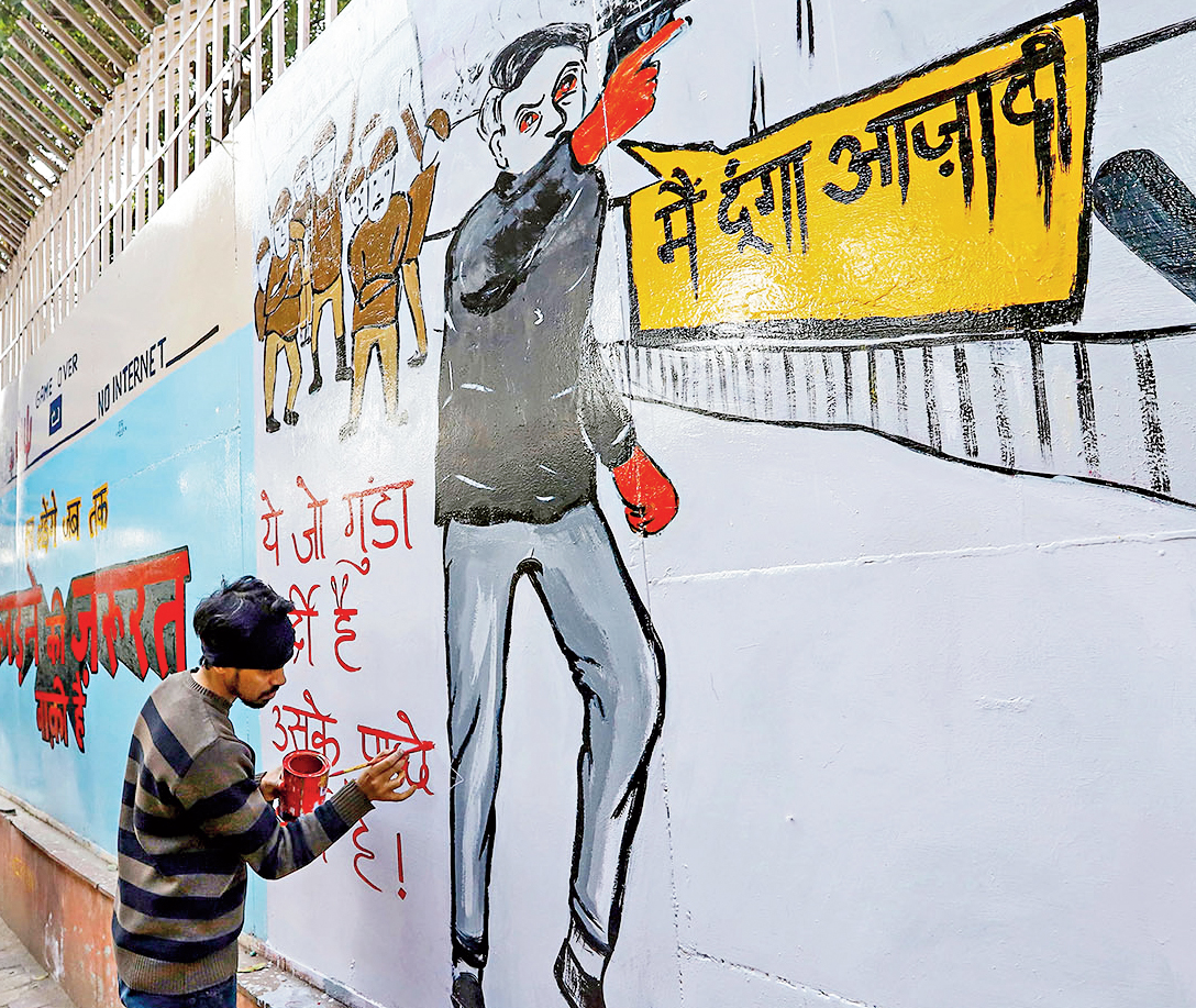 An activist paints graffiti on a wall to protest against the recent incidents of firing at Jamia Millia Islamia and Shaheen Bagh, in New Delhi, Monday, February 03, 2020.