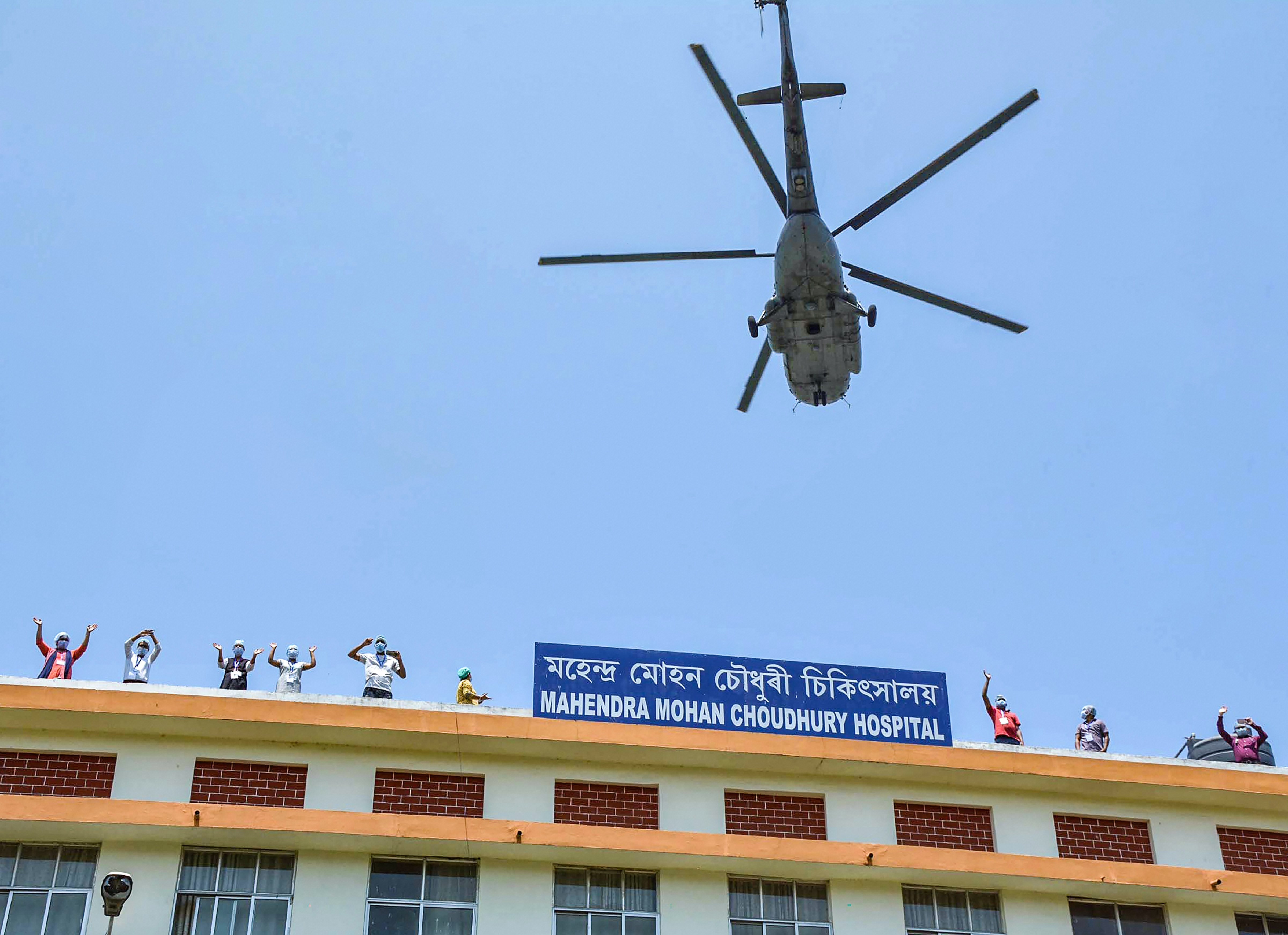 Medics wave as an Indian Air Force (IAF) helicopter showers flower petals to express gratitude towards the frontline workers for their contribution in Indias fight against COVID-19 in Guwahati on Sunday, May 3, 2020.