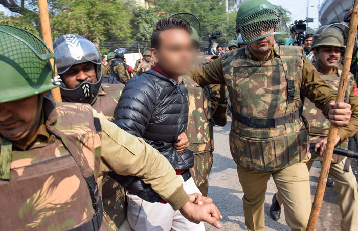 Police detain a person (face blurred by news agency as his being an adult could not be ascertained), after he allegedly brandished a gun and opened fire towards students protesting against the Citizenship Amendment Act, near Jamia Millia Islamia University, in New Delhi.