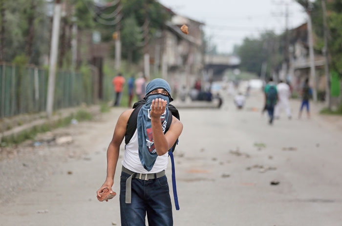 A youth tries to catch a stone thrown at him during a protest in Srinagar on Friday