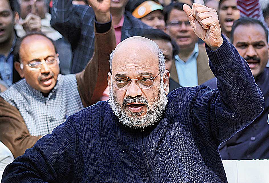 Amit Shah clenches his fist while chanting pro-India slogans before the start of Modi's interaction with party workers in New Delhi on Thursday.