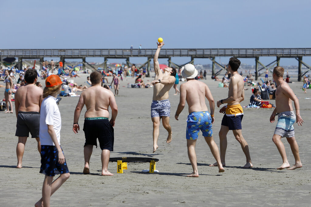 Despite warnings from government officials about taking caution and self distancing because of coronavirus, beach goers enjoy the Isle of Palms beach, Friday, March 20, 2020, in Isle of Palms, S.C. City authorities are restricting access to the popular beach from 7 a.m. to 7 p.m. daily starting Saturday to help stop the spread of the coronavirus.