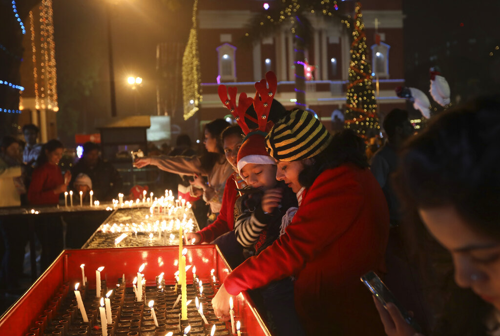 Indians light candles outside the Sacred Heart Cathedral on Christmas eve in New Delhi, India, Tuesday, Dec. 24, 2019.