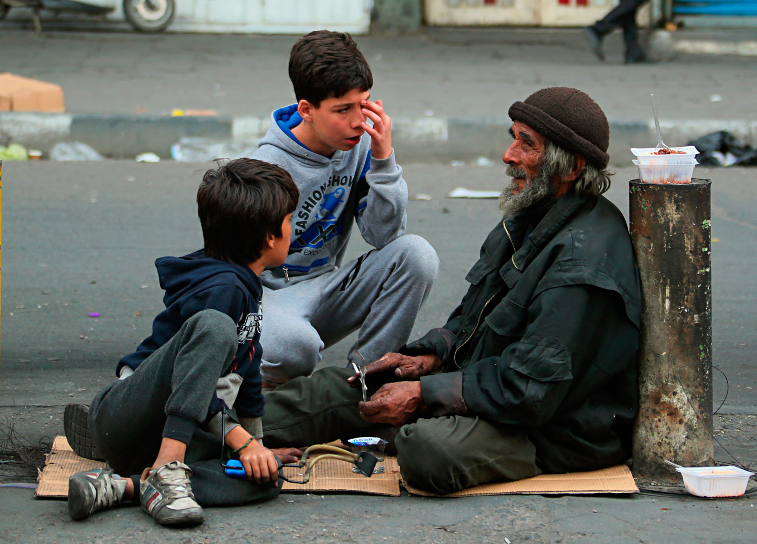 Two younger protesters talk with an older man during ongoing anti-government protests in Baghdad, Iraq