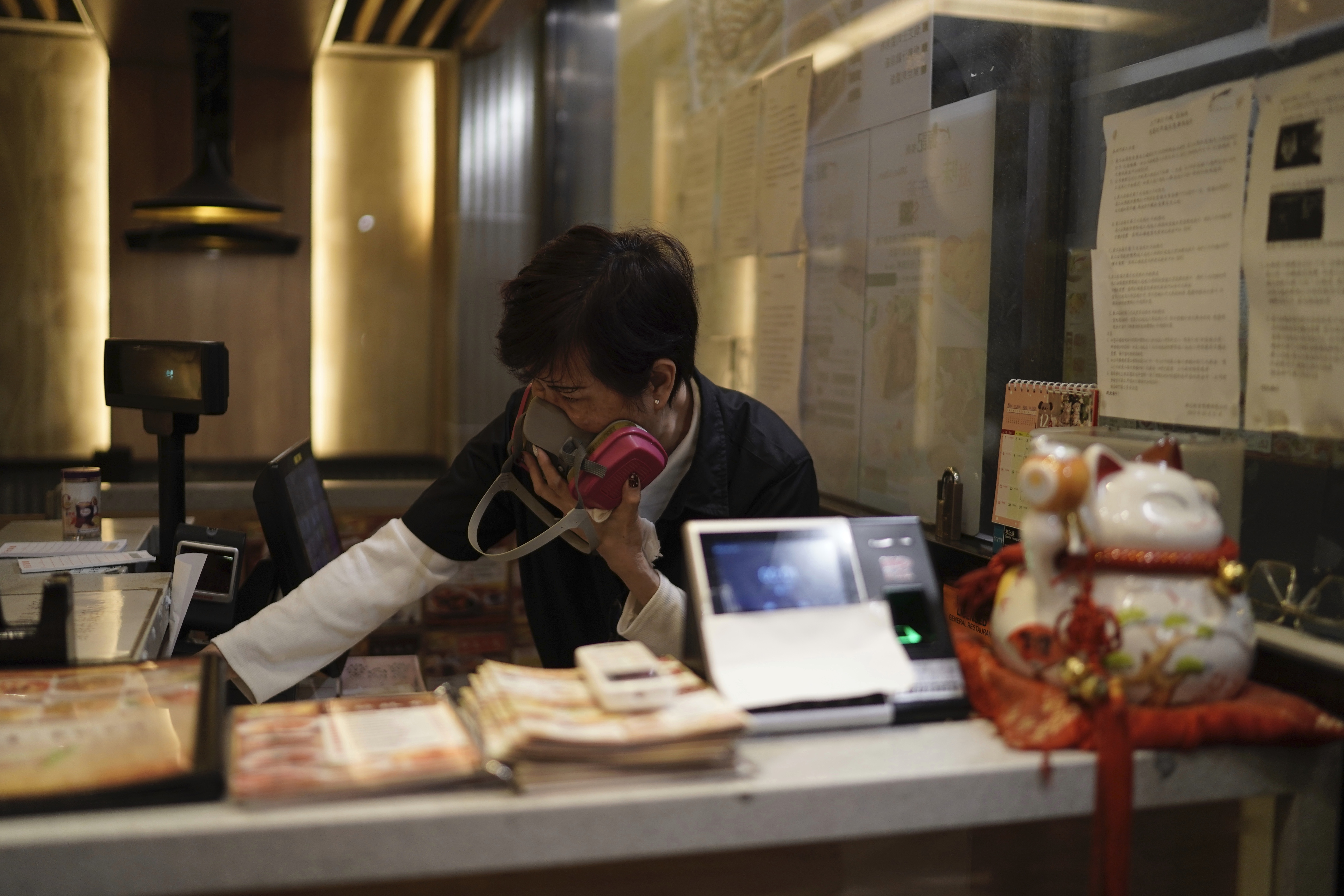 A cashier in a restaurant reacts to tear gas as police confront protesters on Christmas Eve in Hong Kong on December 24, 2019.
