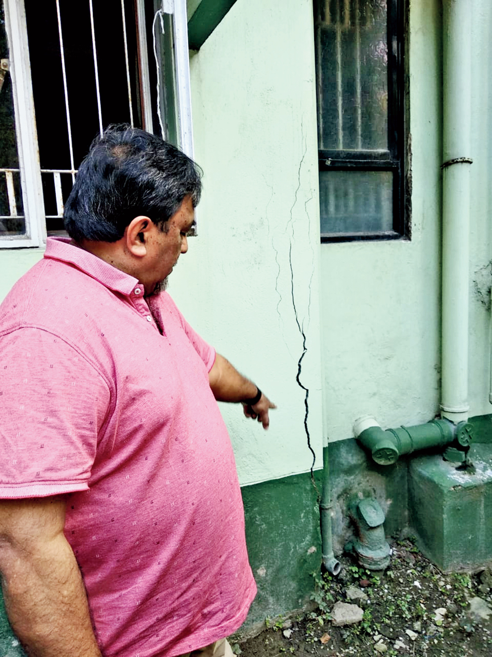 A resident points at a crack in a building near the construction
