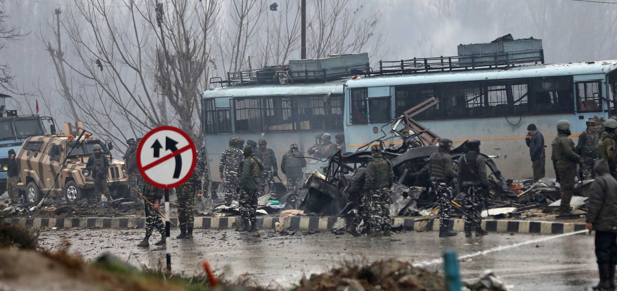 Soldiers stand by the wreckage of a bus after an explosion in Pampore on Thursday.