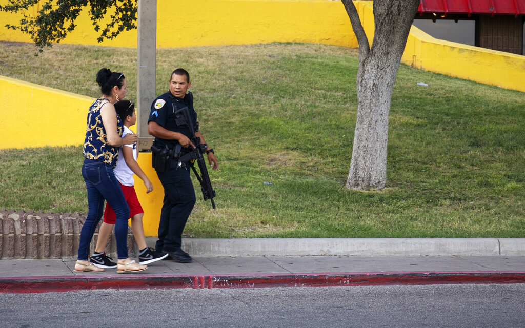 A police officer escort bystanders away from an area investigated for a shooting in Odessa, Texas, on Saturday, August 31, 2019, following a deadly shooting