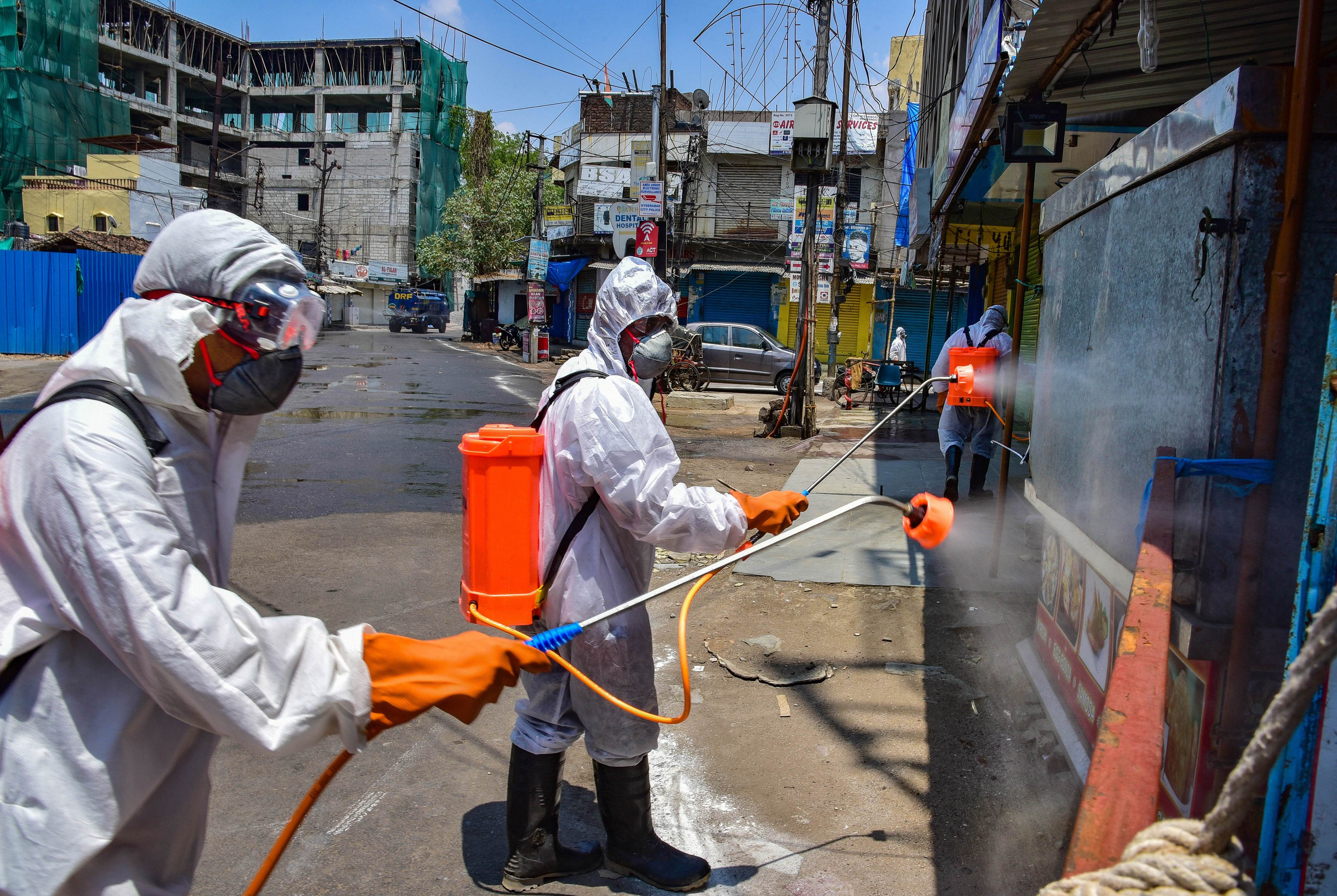 Greater Hyderabad Municipal Corporation (GHMC) workers spray disinfectant at a containment area, during a nationwide lockdown in the wake of coronavirus pandemic, in Hyderabad, Sunday, April 26, 2020