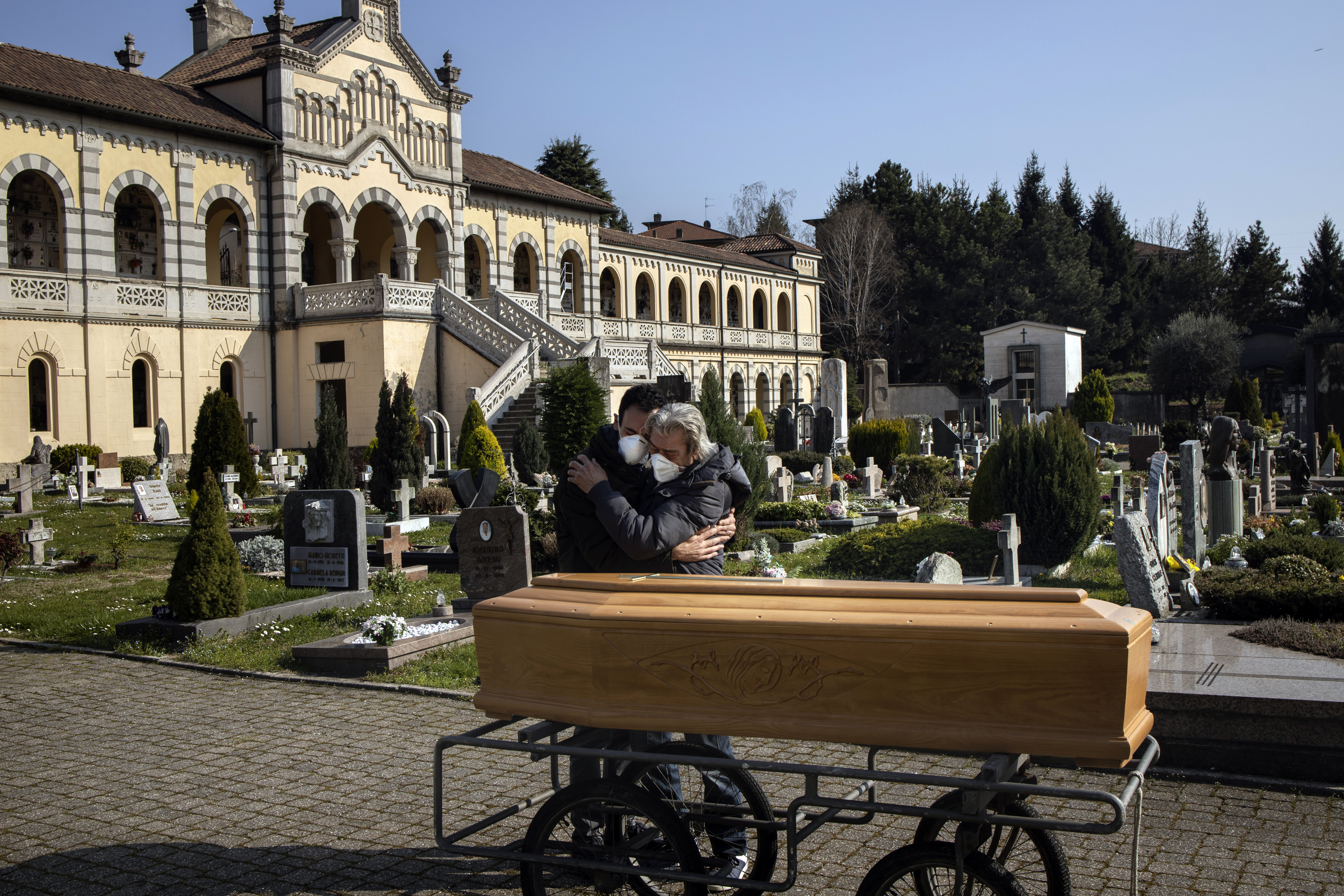 The husband and son of Teresina Gregis mourn after her funeral in Alzano Lombardo, Italy, March 21, 2020. Gregis, who had pre-existing heart and respiratory problems, died at home without being tested for the coronavirus.