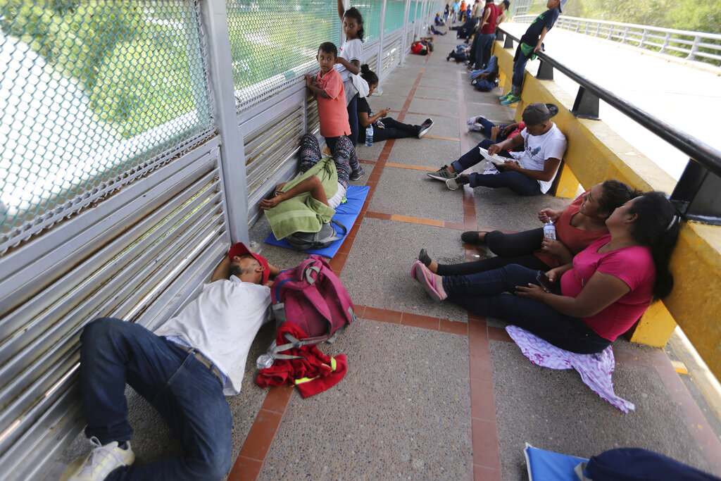 Migrants sleep on the ground after camping out on the Gateway International Bridge that connects downtown Matamoros, Mexico with Brownsville, Thursday, October 10, 2019. Migrants wanting to request asylum are camped out on the international bridge leading from Mexico into Brownsville.