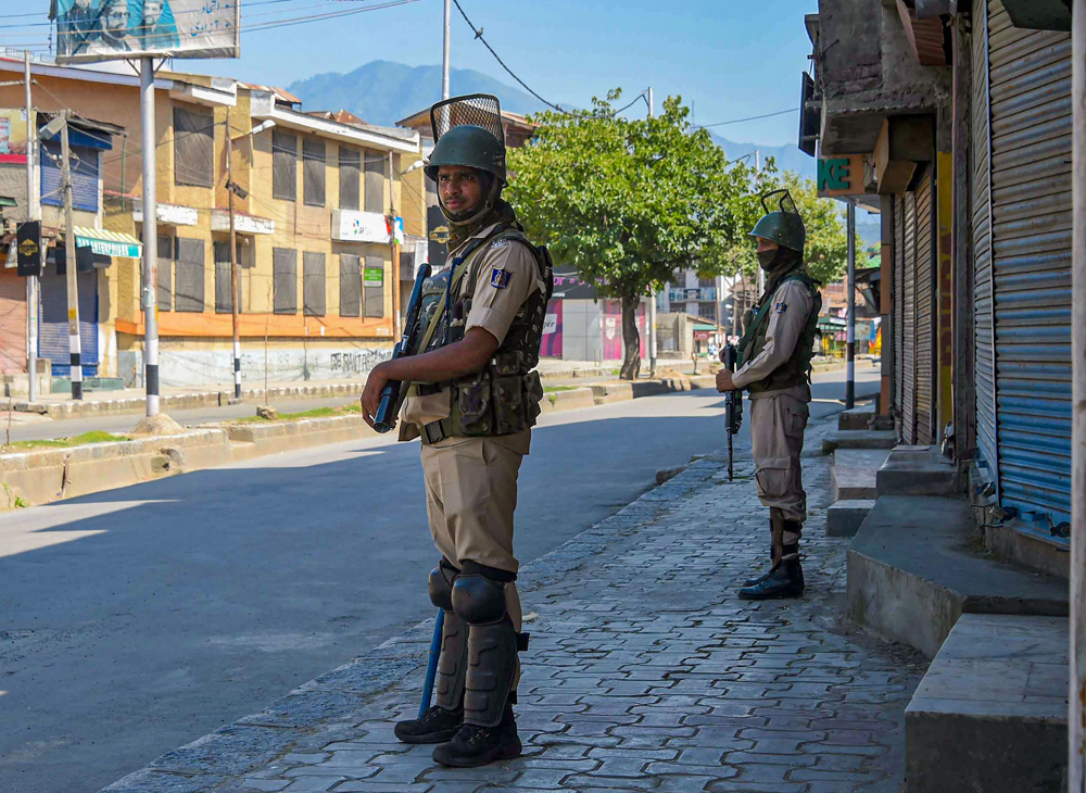 CRPF personnel stand guard in a street in Srinagar, Thursday, August 22, 2019.