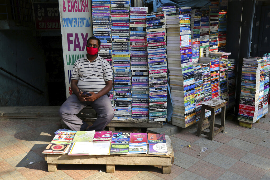A street vendor selling used books wears a face mask as prevention against the coronavirus and waits for customers in Bengaluru, Tuesday, May 26, 2020.