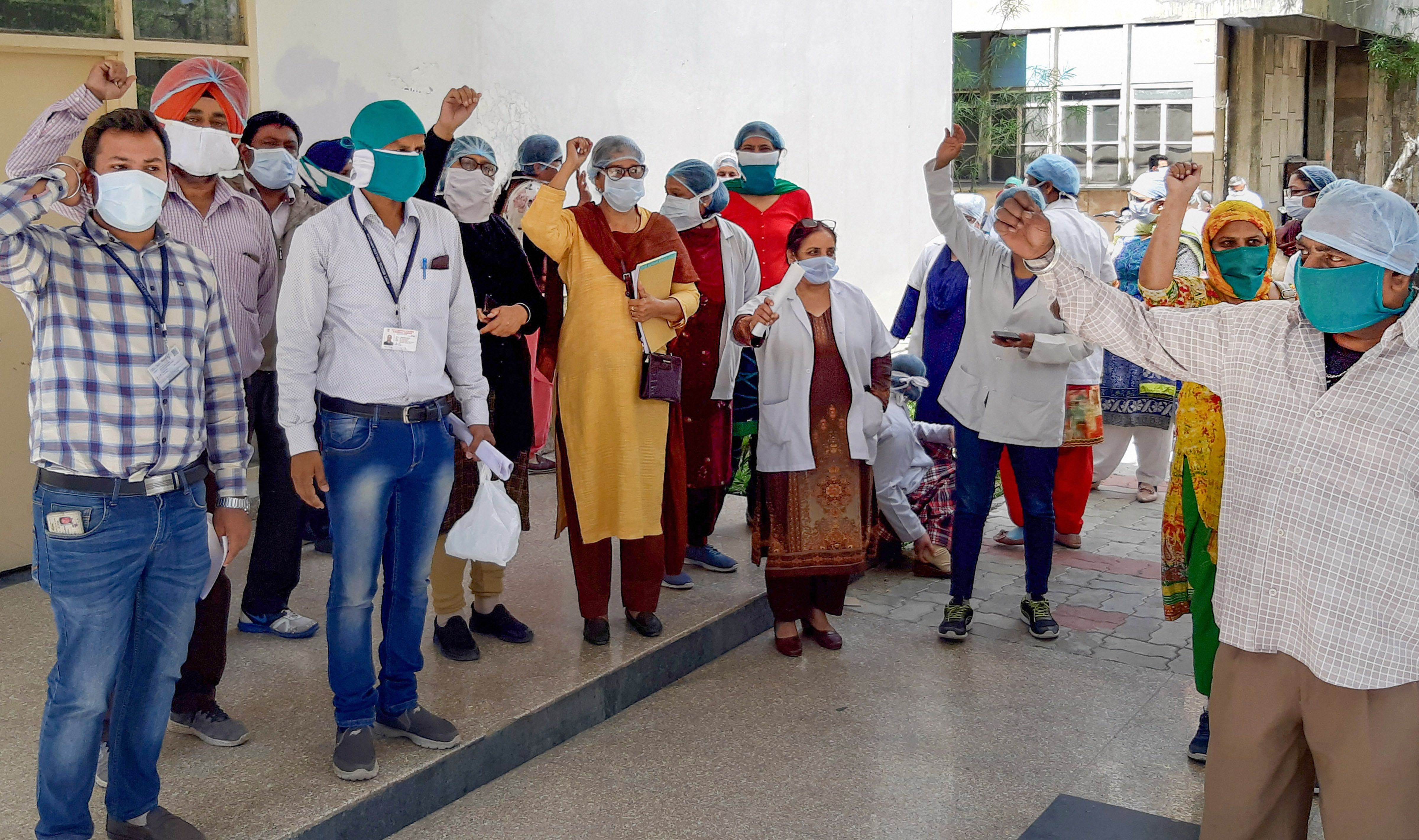 Medical staff of Guru Nanak Dev Hospital stage a protest over the supply of alleged low-quality of Personal Protection Equipment (PPE) and other medical facilities required for the treatment of coronavirus-affected patients, in Amritsar, Friday, April 3, 2020.