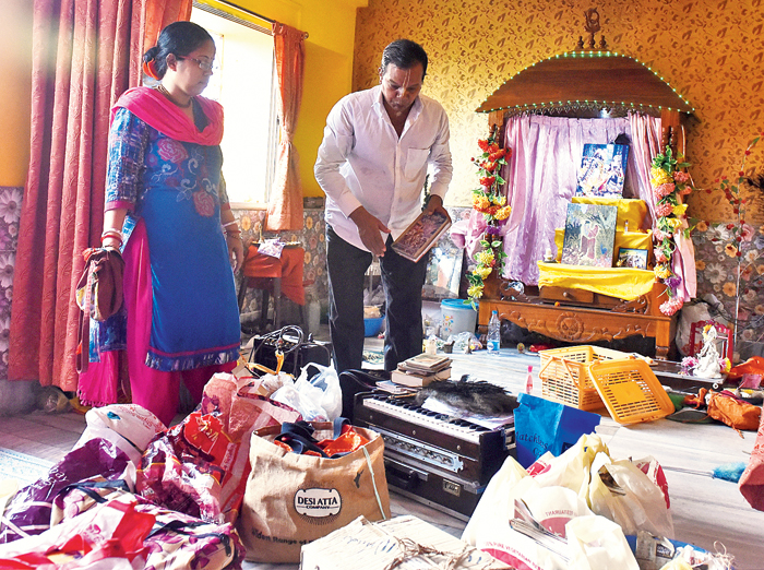 Shyamal Kumar Dutta and his wife pack their belongings and (right) their son Subhankar packs his books at their home on Thursday