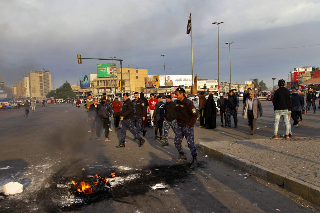 Security forces try to open streets while protesters set fire during a demonstration to protest against the Iranian missile strike, in Baghdad, Iraq, Wednesday, January 8, 2020.