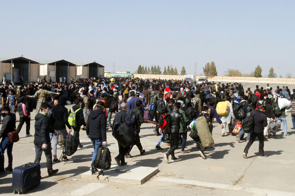 Thousands of Afghan refugees walk as they enter Afghanistan at the Islam Qala border crossing with Iran, in the western Herat Province, Wednesday, March 18, 2020.