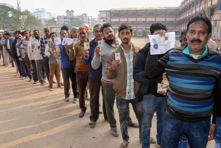 Voters stand in queue flaunting their voter ID during the third phase of Jharkhand Assembly Elections
