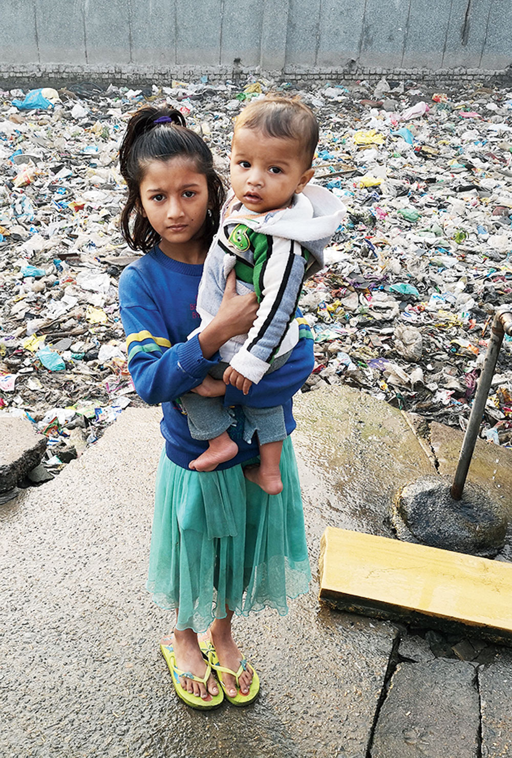 Photographs from the landfill series show children and adults standing against mountains of filth