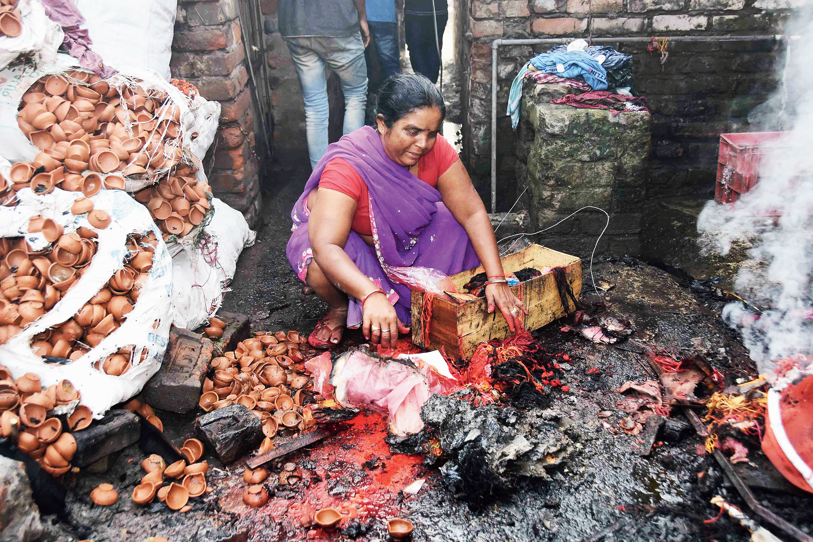 A woman weeps while showing the damaged goods of her shop after a fire near the GPO roundabout in Patna on Sunday.