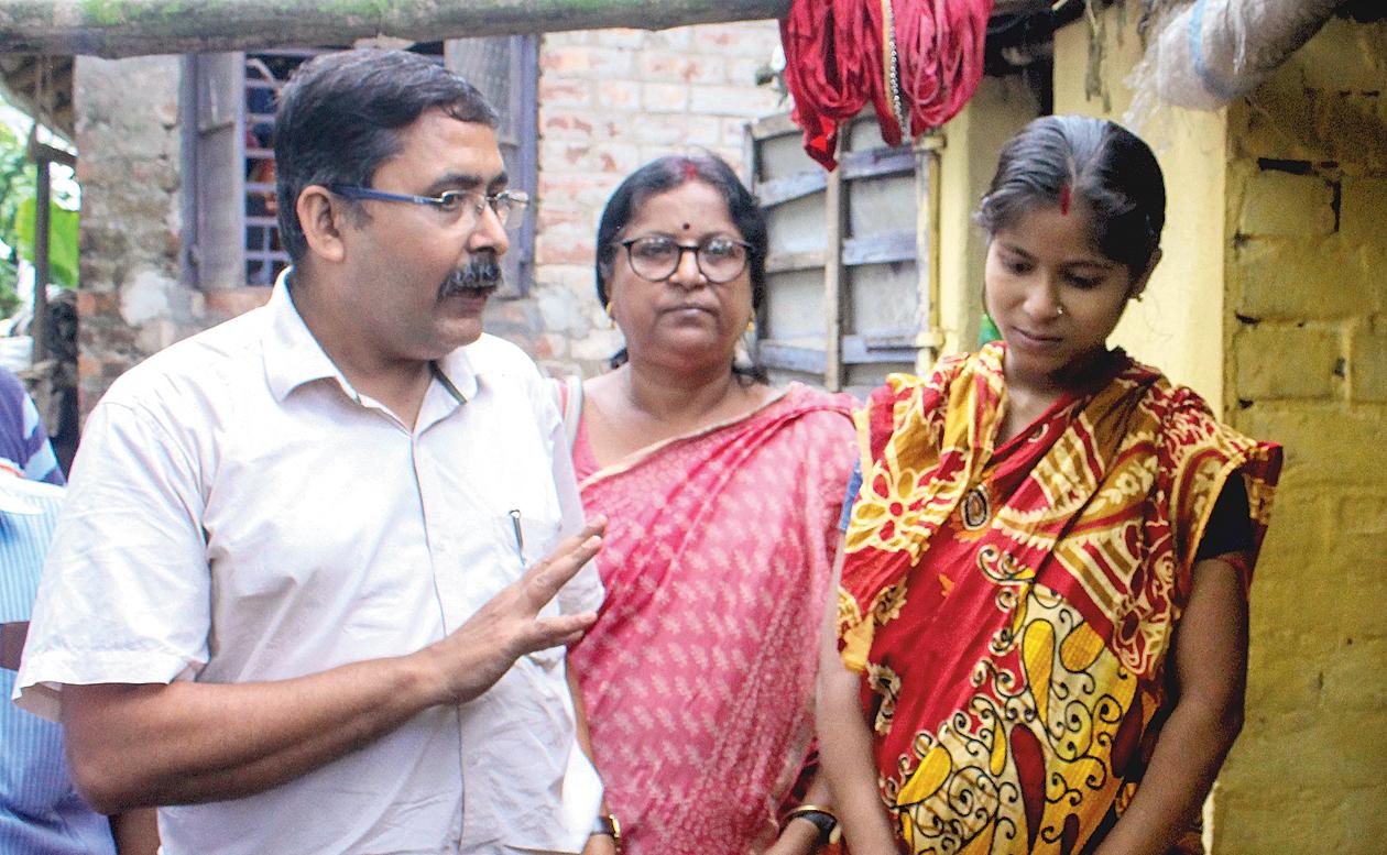Bhaskar Ghosh (left) speaks to Moumita Sandhukhan at her home in Santipur on Monday.