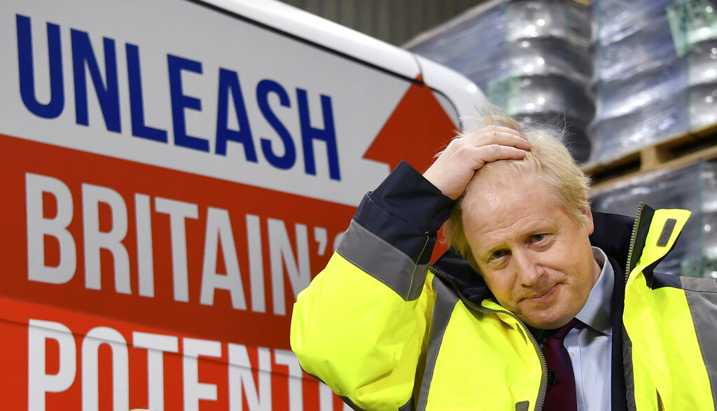 Britain's Prime Minister Boris Johnson gestures as stands by as CEO Alan Ferguson talks, during a question and answer session, part of a General Election campaign visit to Ferguson's Transport in Washington, England, Monday, Dec. 9, 2019.