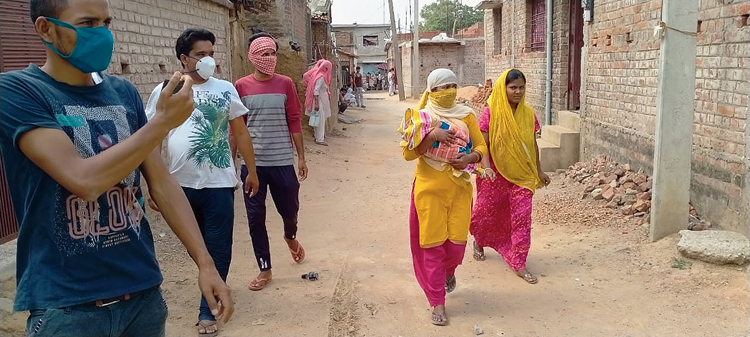 A woman, who recovered from Covid-19, reaches her village Gadokhar in Hazaribagh with her newborn, on Tuesday.