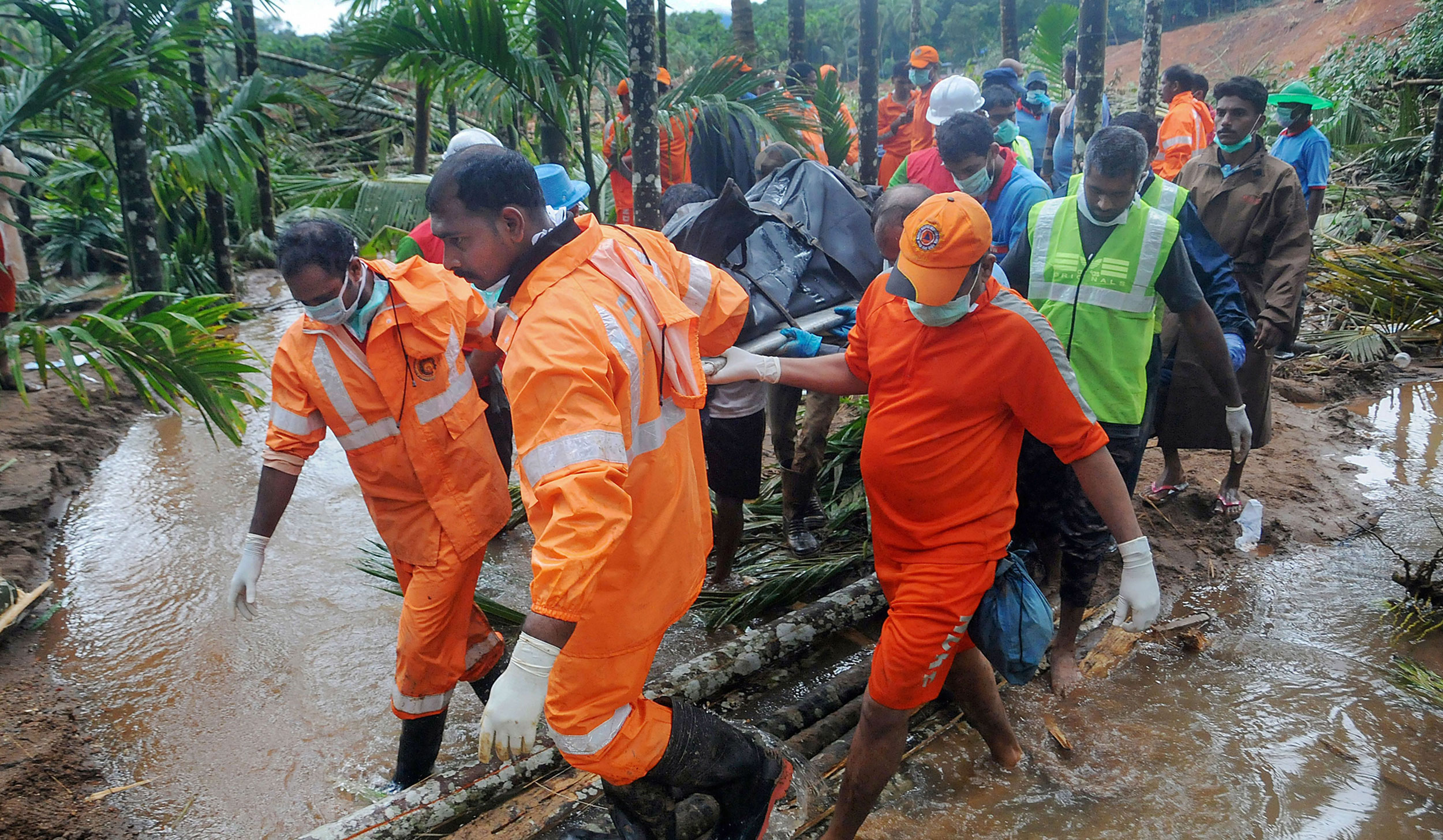 Rescue workers recover a body from a site of the landslide at Kavalappara in Malappuram district on August 14, 2019.