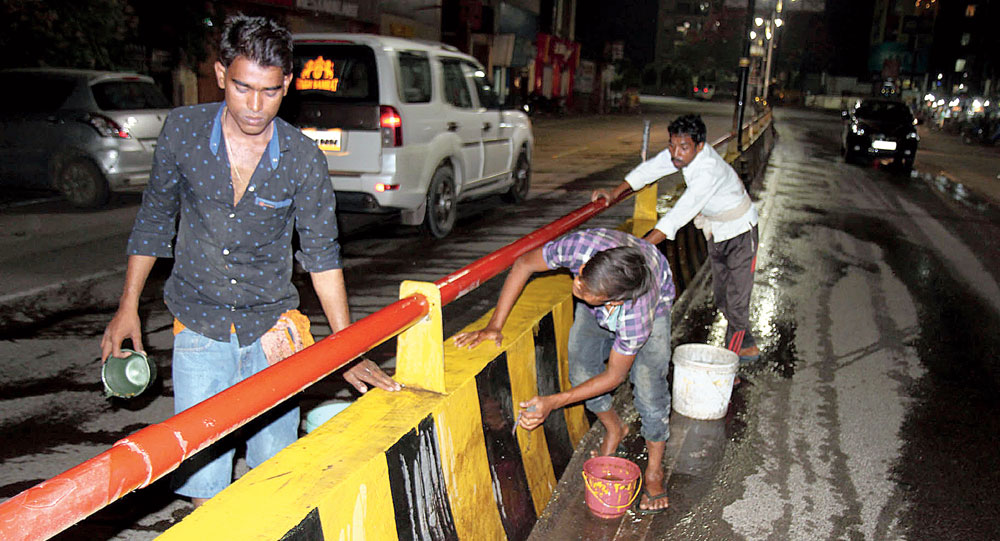 Workers scrub a road divider in Varanasi on Wednesday night