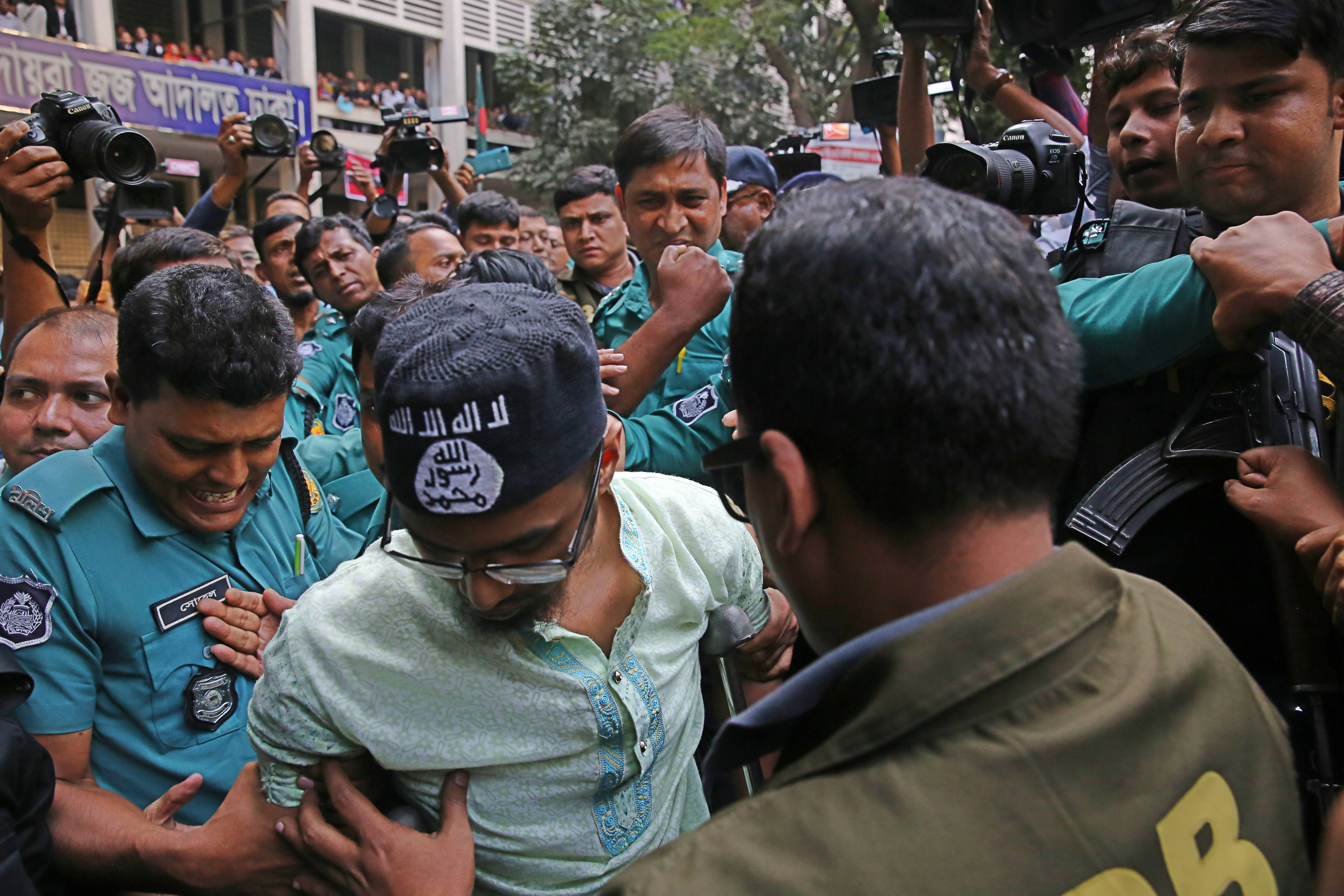 Police escort a member of a banned militant group after he was sentenced to death for an attack on a Dhaka cafe that killed more than 20 people in Wednesday, November 27, 2019