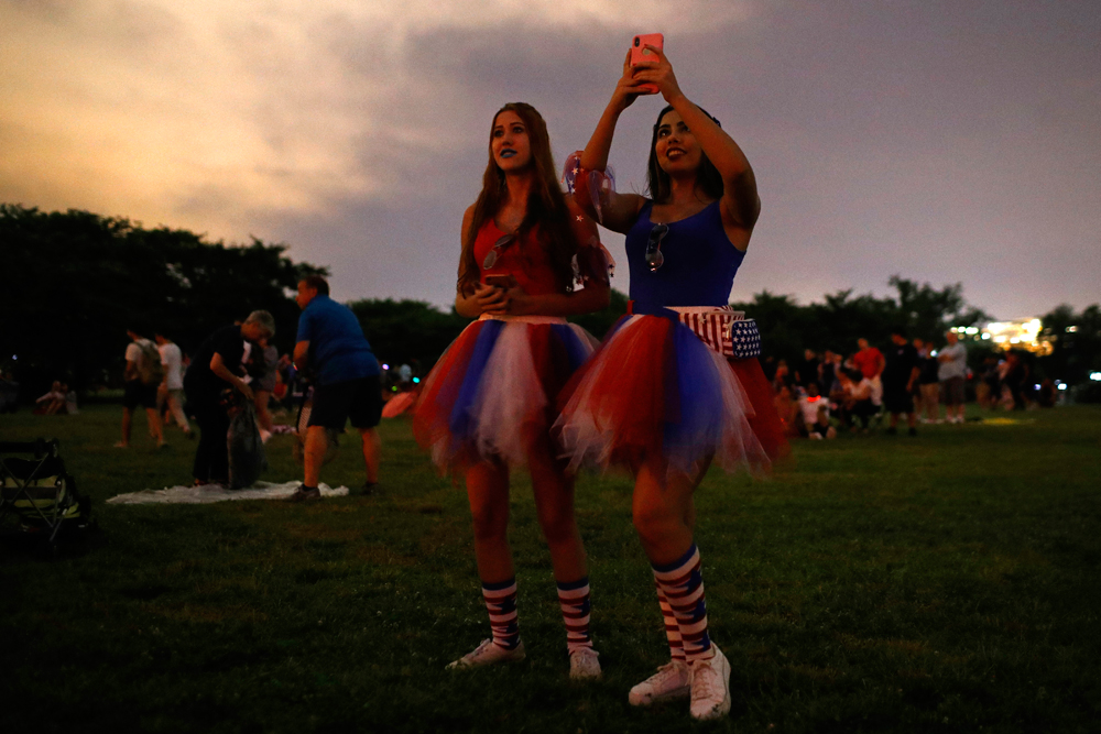 Revellers photograph fireworks during Independence Day celebrations on the National Mall in Washington on Thursday