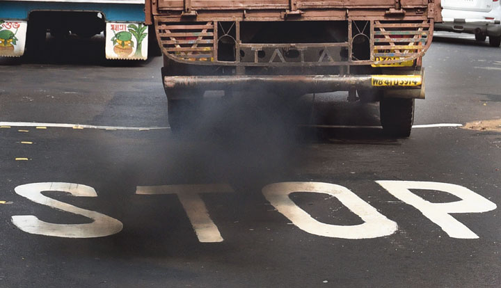 A truck belches out smoke in the city