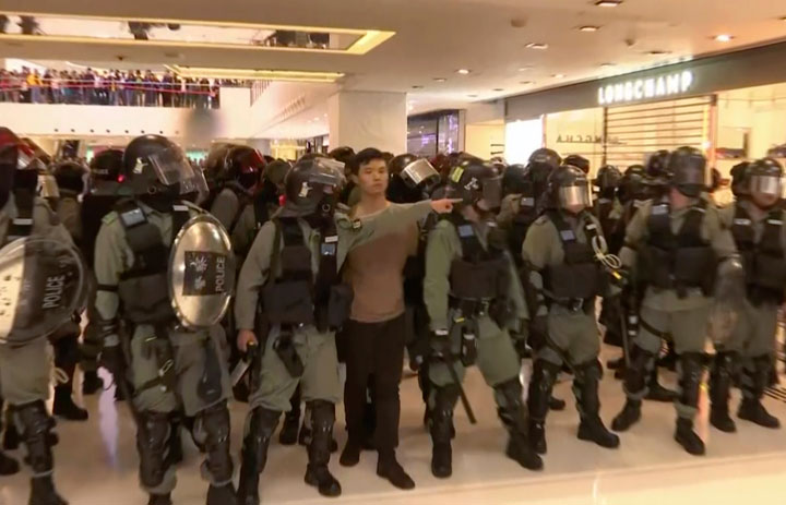 A protester is arrested by police at a shopping mall in Sha Tin district in Hong Kong, with shoppers watch from balconies above, Sunday, December 15