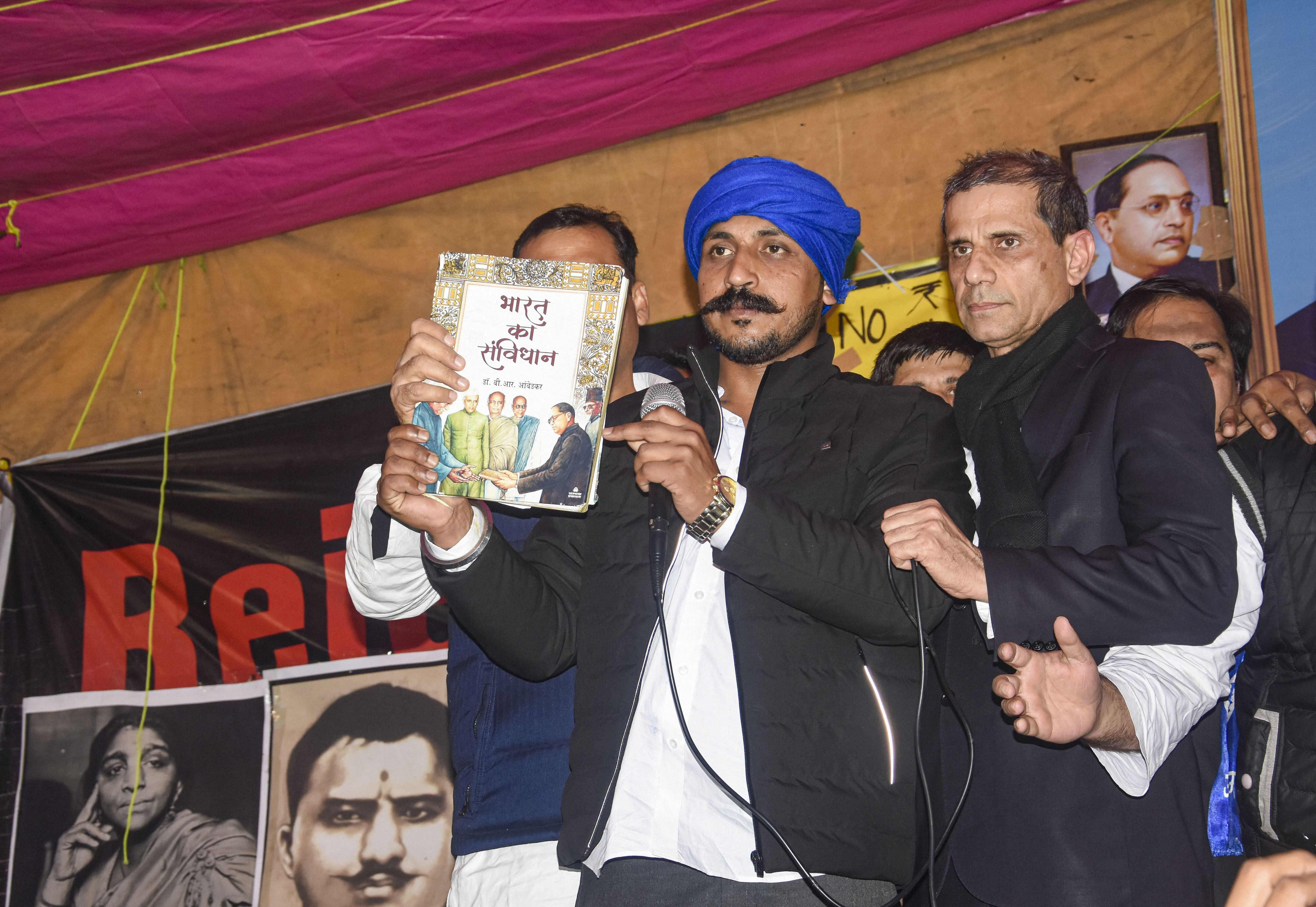 Bhim Army Chief Chandrasekhar Azad holds a copy of the Indian constitution during the ongoing protest against NRC and CAA at Shaheen Bagh in New Delhi, Wednesday, Jan. 22, 2020.