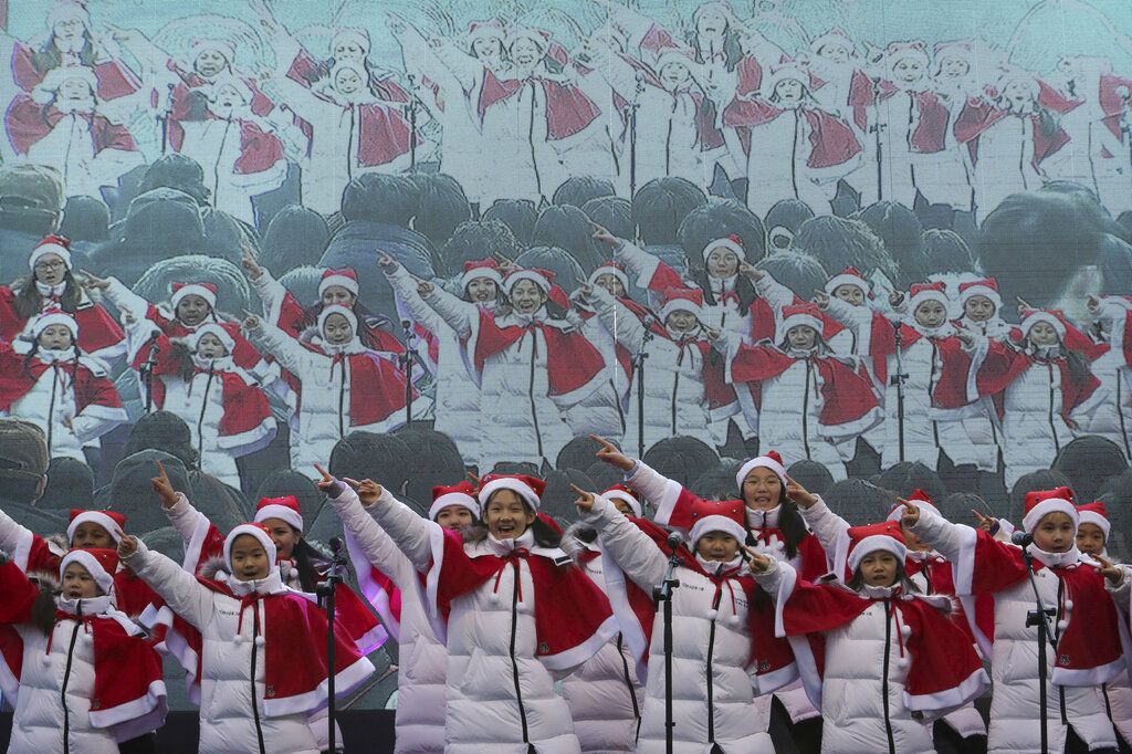 Children sing carols during a Christmas charity event as they gather to deliver gifts for the poor in Seoul, South Korea, Tuesday, Dec. 24, 2019.