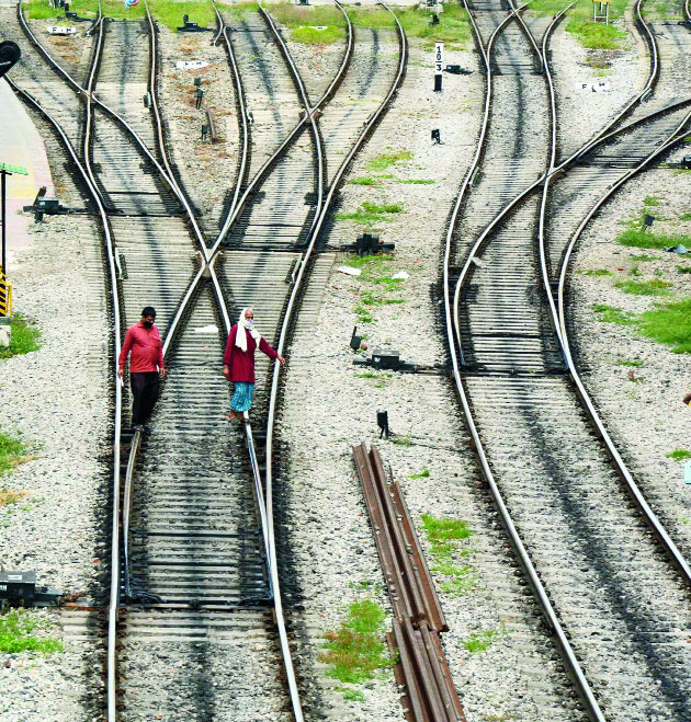 Crossing paths: Workers cross the railway tracks in Guwahati on Monday.