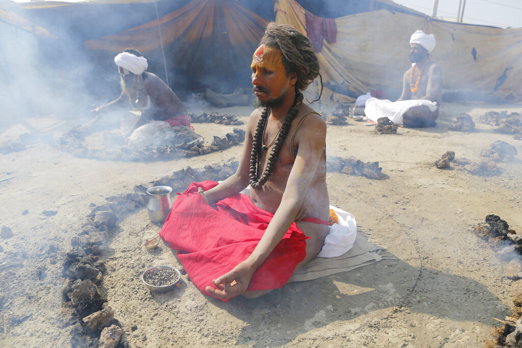Hindu holy men burn dried cow dung cakes as they perform a ritual at the Sangam, the confluence of rivers Ganges and Yamuna, on Basant Panchami day at the annual traditional fair of Magh Mela Prayagraj